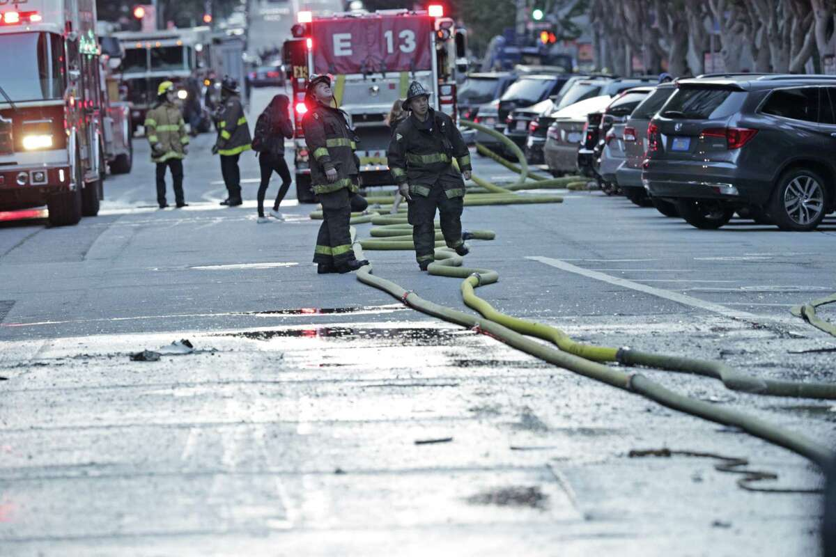 Fire hoses laying in the street as firefighters finish working a fire in a high-rise apartment building on Davis Court in San Francisco on Monday Oct. 22, 2018.