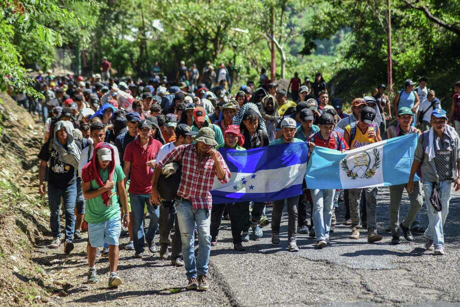 Migrantes hondureños participan en una caravana que se dirige a los Estados Unidos sosteniendo banderas hondureñas y guatemaltecas en Quezaltepeque, Chiquimula, Guatemala, el 22 de octubre de 2018. Photo: Orlando Estrada /AFP /Getty Images / AFP or licensors