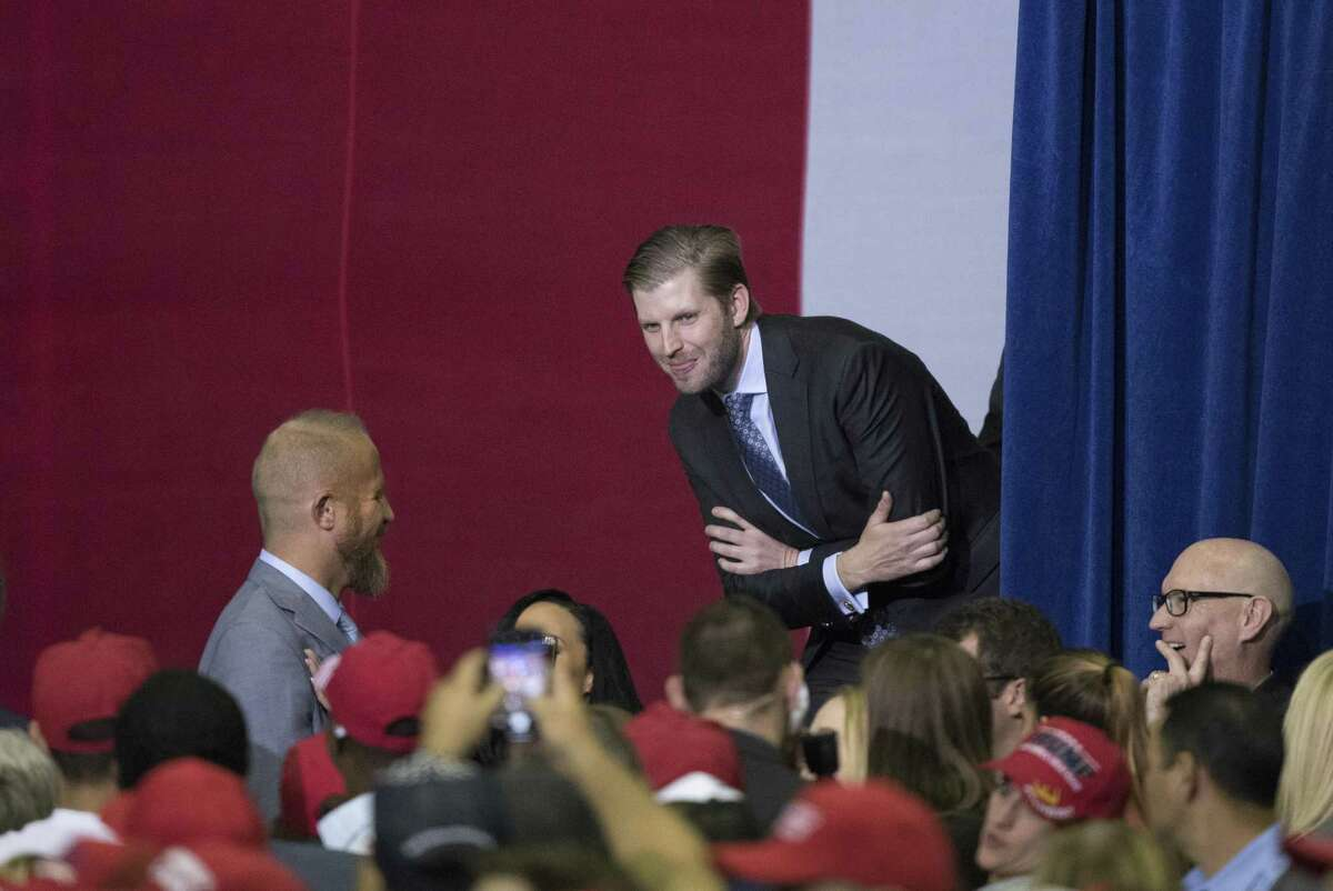 Eric Trump peeks out smiling at the audience as his wife Lara Trump gives a speech during a rally on Monday, October 22, 2018 at the Toyota Center in Houston, Texas.