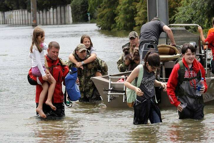 Residents are rescued from their homes surrounded by floodwaters from Hurricane Harvey on Sunday, Aug. 27, 2017, in Houston, Texas.
