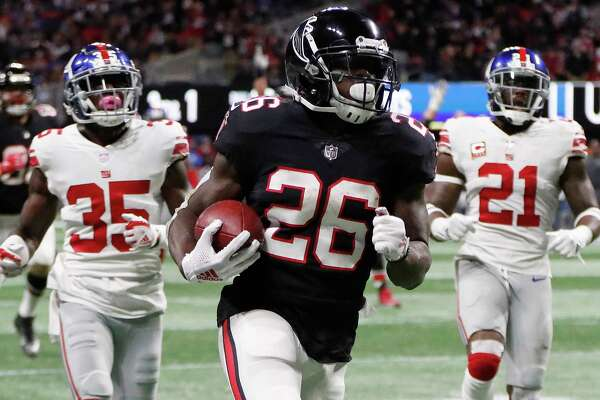 Atlanta Falcons running back Tevin Coleman (26) runs into the end zone for a touchdown against New York Giants free safety Curtis Riley (35) and strong safety Landon Collins (21) during the second half of an NFL football game, Monday, Oct. 22, 2018, in Atlanta.