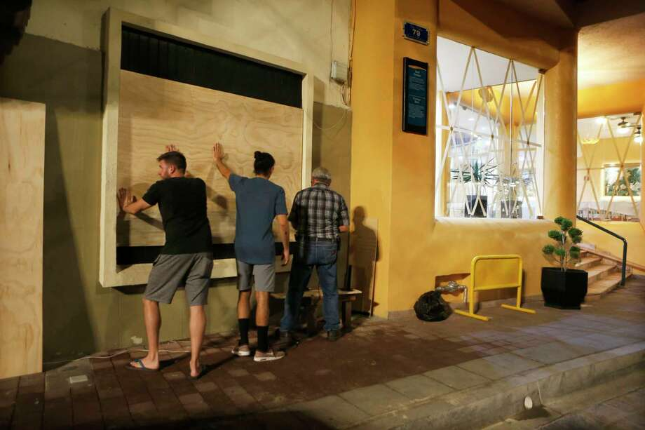 Residents cover windows with wood ahead of Hurricane Willa in Mazatlan, Mexico, Monday, Oct. 22, 2018. A potential catastrophic Hurricane Willa swept toward Mexico's Pacific coast Monday night, threatening a stretch of high-rise resort hotels, surfing beaches and fishing villages. Photo: Marco Ugarte, AP / Copyright 2018 The Associated Press. All rights reserved.