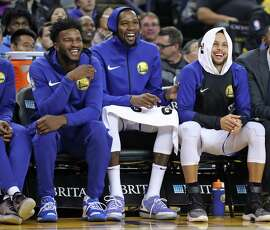 Golden State Warriors' Jordan Bell, Kevin Durant and Stephen Curry enjoy the view from the bench in 2nd quarter against Phoenix Suns during NBA game at Oracle Arena in Oakland, Calif.. on Monday, October 22, 2018.