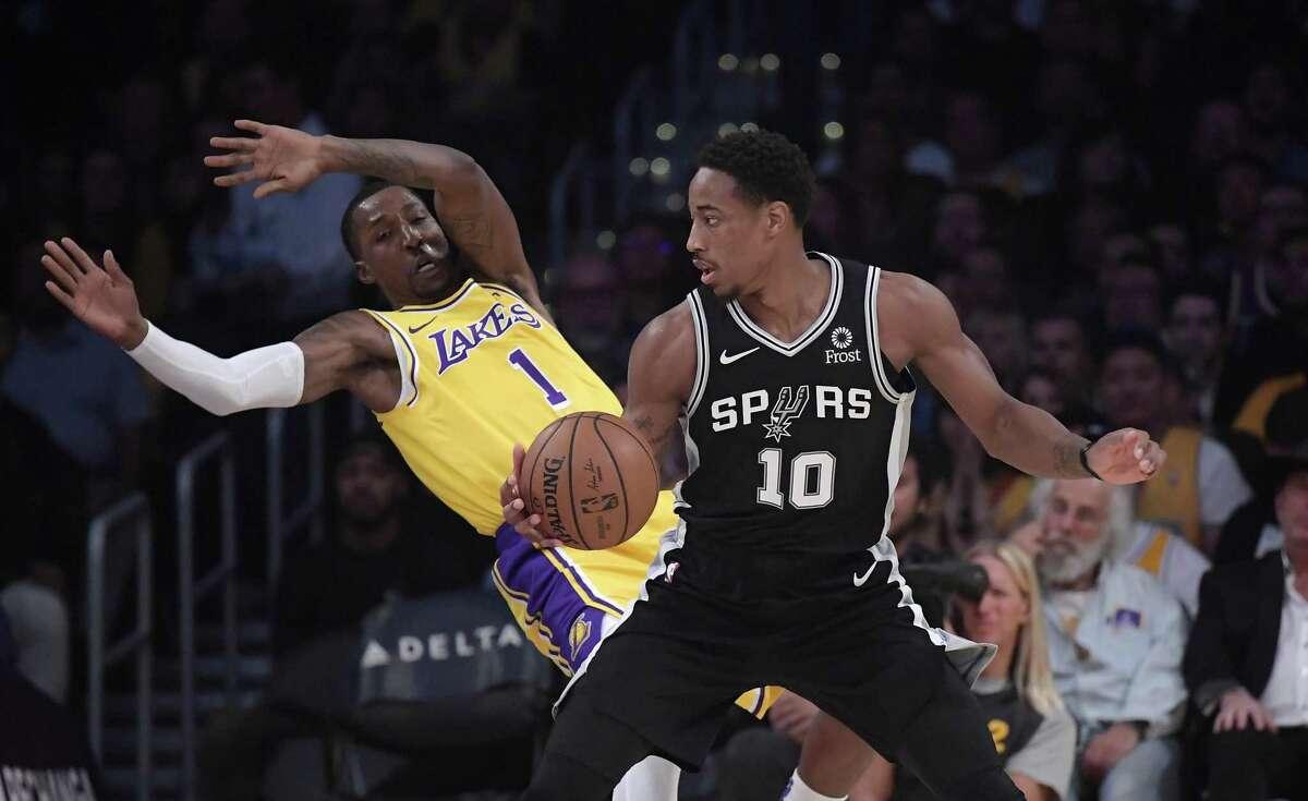 Los Angeles Lakers guard Kentavious Caldwell-Pope, left, falls as San Antonio Spurs guard DeMar DeRozan drives toward the basket during the first half of an NBA basketball game Monday, Oct. 22, 2018, in Los Angeles. (AP Photo/Mark J. Terrill)