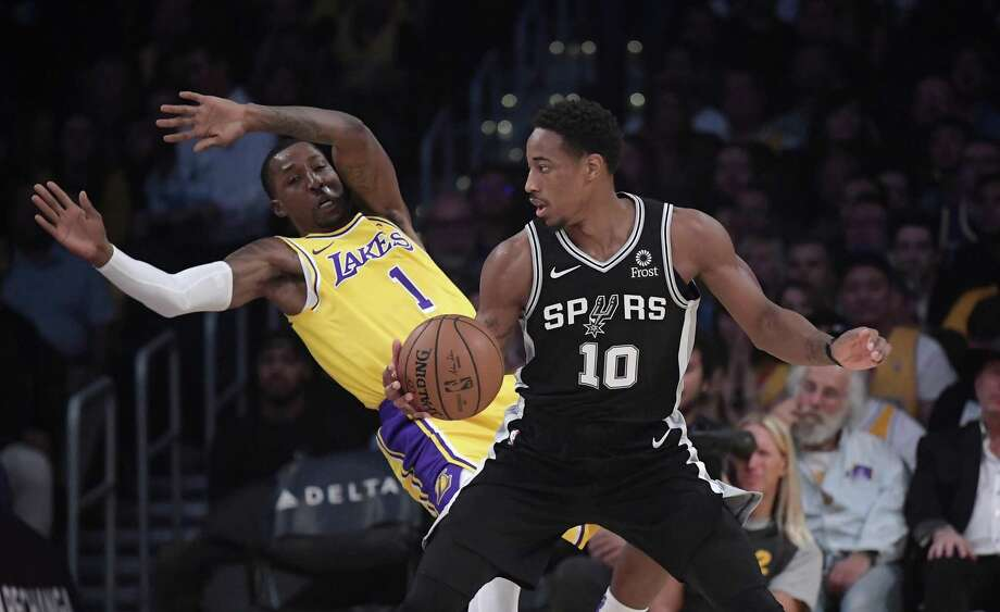 Los Angeles Lakers guard Kentavious Caldwell-Pope, left, falls as San Antonio Spurs guard DeMar DeRozan drives toward the basket during the first half of an NBA basketball game Monday, Oct. 22, 2018, in Los Angeles. (AP Photo/Mark J. Terrill) Photo: Mark J. Terrill, STF / Associated Press / Copyright 2018 The Associated Press. All rights reserved.