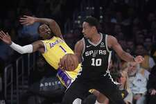 Los Angeles Lakers guard Kentavious Caldwell-Pope, left, falls as San Antonio Spurs guard DeMar DeRozan drives toward the basket during the first half of an NBA basketball game Monday, Oct. 22, 2018, in Los Angeles. (AP Photo/Mark J. Terrill)