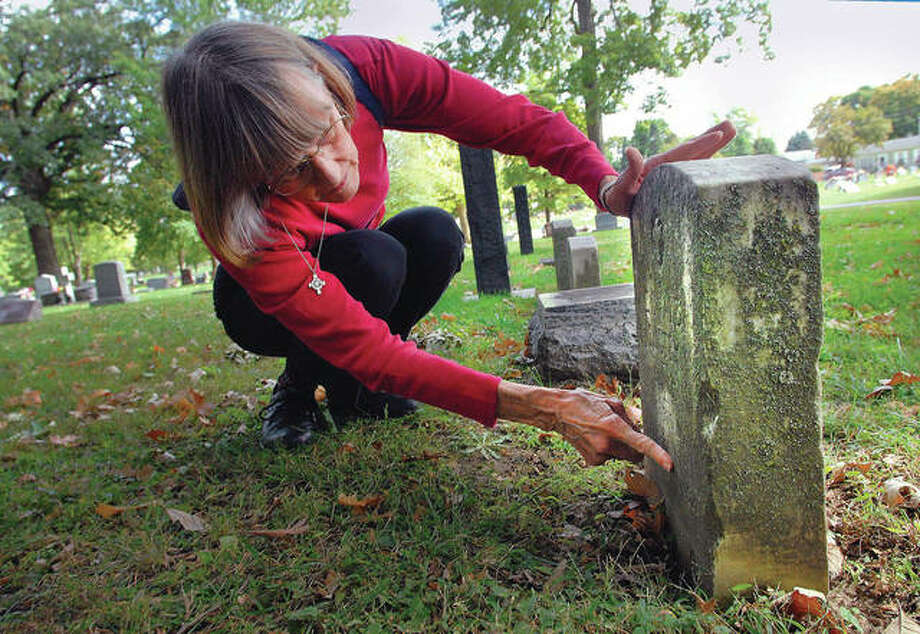 Christine Gruber notes the condition of the tombstone of Donald Luster, a member of the all-black 370th Infantry Division, at Evergreen Memorial Cemetery in Bloomington. Gruber and her husband, Gary, have been restoring several of the headstones that have been obscured by decades of weather. Photo: David Proeber | The Pantagraph (AP)