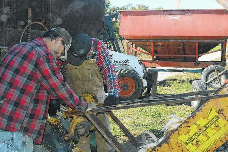 Dave Hill and Gary Harris load corn into a vintage corn sheller on part of the farm Harris works in Virginia. They are part of a small group who decided to pick and shell a few acres of corn the old-fashioned way.