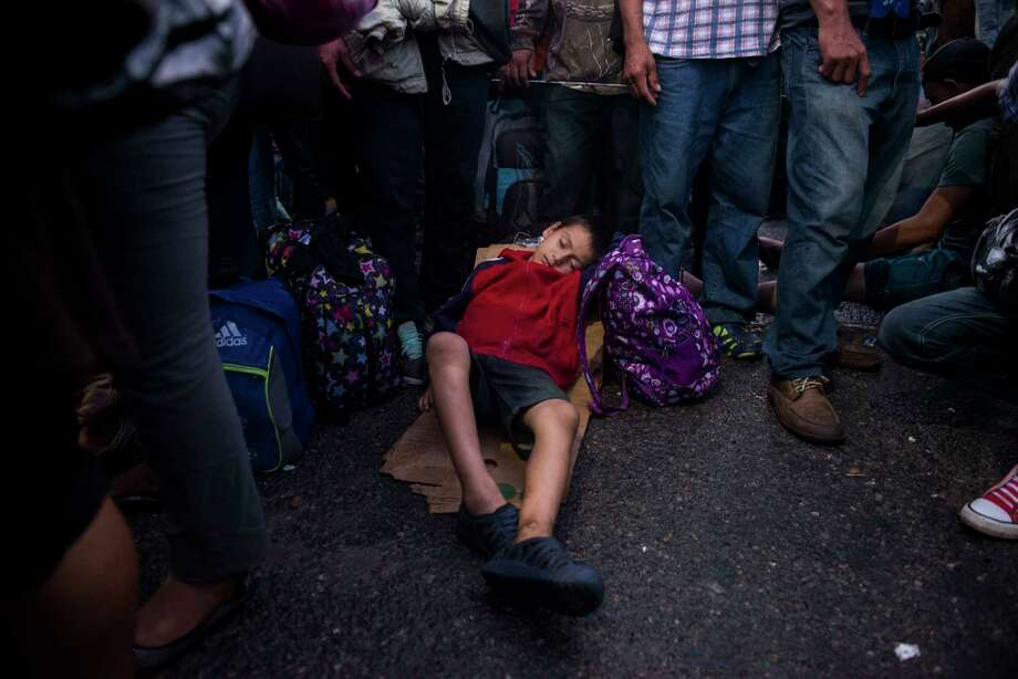 A migrant child sleeps on a piece of cardboard as the group he is traveling with waits to be attended by Mexican immigration authorities on a bridge that stretches over the Suchiate River, connecting Guatemala and Mexico, in Tecun Uman, Guatemala, Monday, Oct. 22, 2018. Photo: Oliver De Ros, AP / Copyright 2018 The Associated Press. All rights reserved