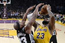 Los Angeles Lakers forward LeBron James, right, shoots as San Antonio Spurs forward Dante Cunningham defends during the second half of an NBA basketball game Monday, Oct. 22, 2018, in Los Angeles. The Spurs won 143-142. (AP Photo/Mark J. Terrill)