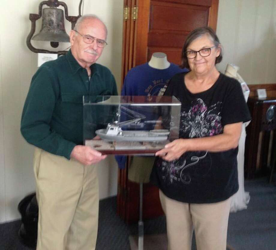 David McDonald and Sue Schweitzer, president of the Bay Port Area Historical Society, hold a replica of the Bay Port fishing boat Osprey. David McDonald of Bad Axe made the boat. It can be seen at the Bay Port Area Historical Museum. (Submitted Photo)