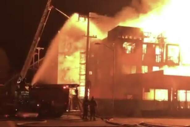 Flames and smoke rise from a fire at an apartment complex under construction at West Grand Avenue and Market Street in Oakland, Calif., early Tuesday, Oct. 23, 2018.