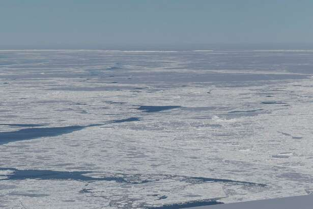 """""""A tabular iceberg can be seen on the right, floating among sea ice just off of the Larsen C ice shelf. The iceberg's sharp angles and flat surface indicate that it probably recently calved from the ice shelf,"""" NASA reports."""
