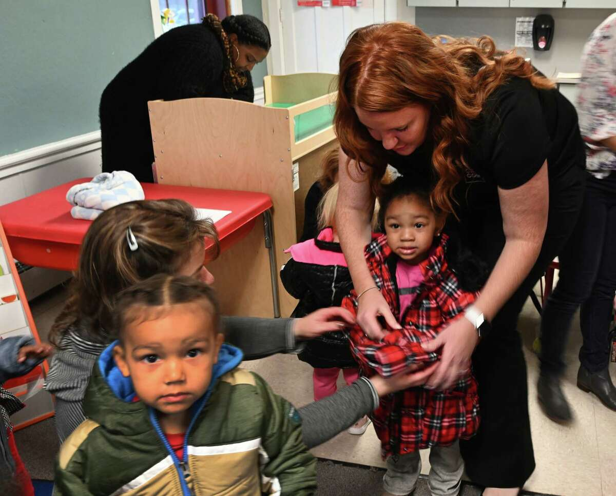 Lauren Tatro assists Mai'Ahlilly Lewis with a new coat at the Lansingburgh Family Resources as Joel Torres, foreground is focused on the photographer Tuesday Oct.23, 2018 in Troy, N.Y. CAPCOM Federal Credit Union and its charitable giving arm, the CAP COM Cares Foundation will donate nearly 300 new winter coats to children in need who attend the Commission on Economic Opportunity's(CEO) Head Start Program. (Skip Dickstein/Times Union)
