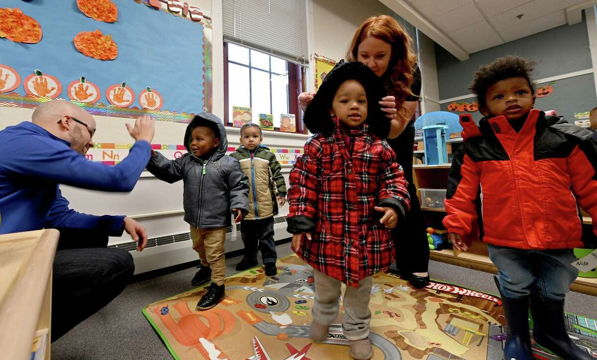 Lauren Tatro, second from right, assists Mai'Ahlilly Lewis with a new coat as other students get a chance to try on their new coats at the Lansingburgh Family Resources Tuesday Oct.23, 2018 in Troy, N.Y. CAPCOM Federal Credit Union and it's charitable giving arm, the CAP COM Cares Foundation will donate nearly 300 new winter coats to children in need who attend the Commission on Economic Opportunity's(CEO) Head Start Program. (Skip Dickstein/Times Union)