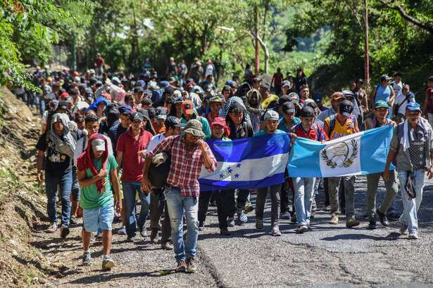 Honduran migrants take part in a new caravan heading to the US with Honduran and Guatemalan national flags in Quezaltepeque, Chiquimula, Guatemala on October 22, 2018. - US President Donald Trump on Monday called the migrant caravan heading toward the US-Mexico border a national emergency, saying he has alerted the US border patrol and military.