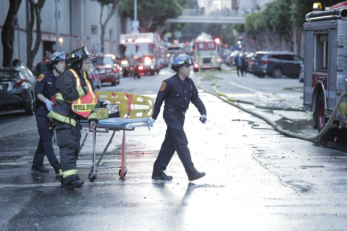 San Francisco paramedics bring a gurney to the scene of a three alarm fire in a high-rise apartment building on Davis Court in San Francisco on Monday Oct. 22, 2018.