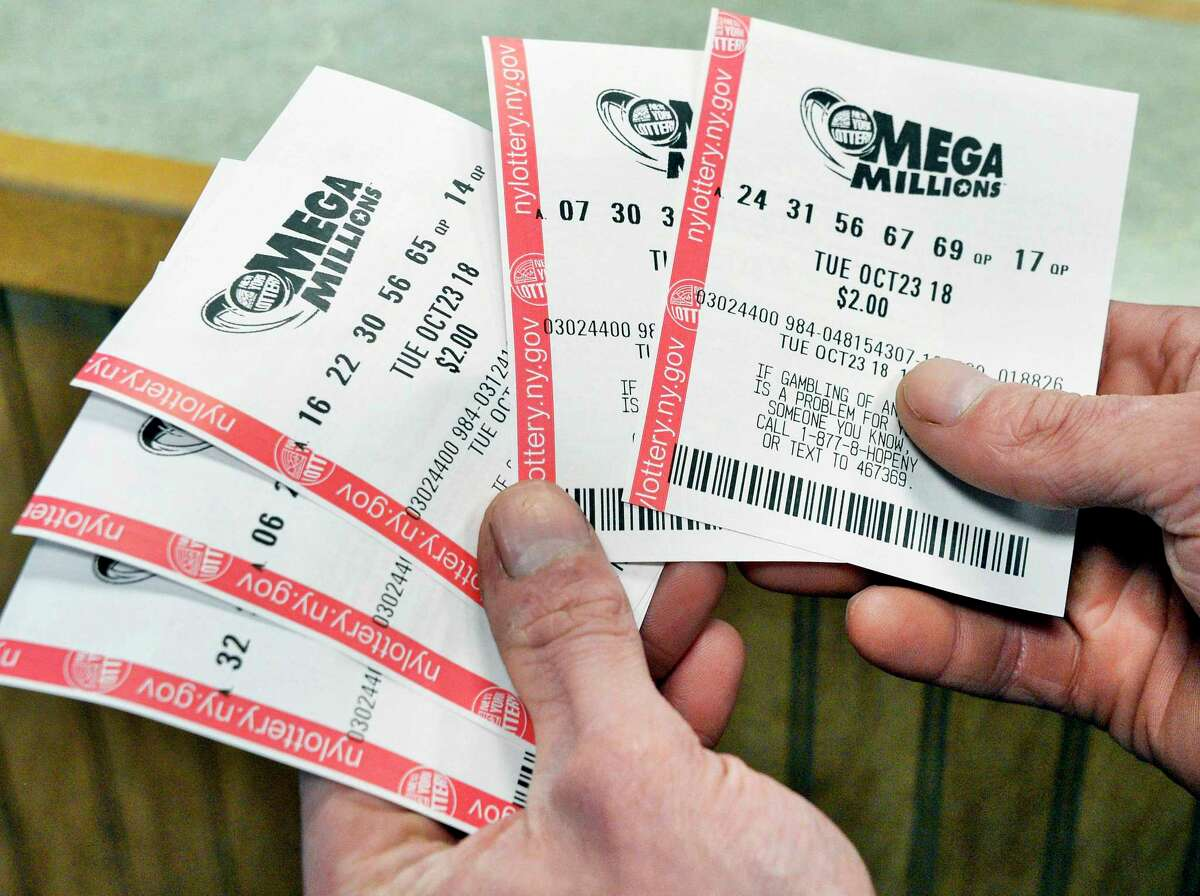 Adam Gerling of Albany checks his Mega Millions tickets at Edleez Tobacco in Stuyvesant Plaza Tuesday Oct. 23, 2018 in Albany, NY. (John Carl D'Annibale/Times Union)