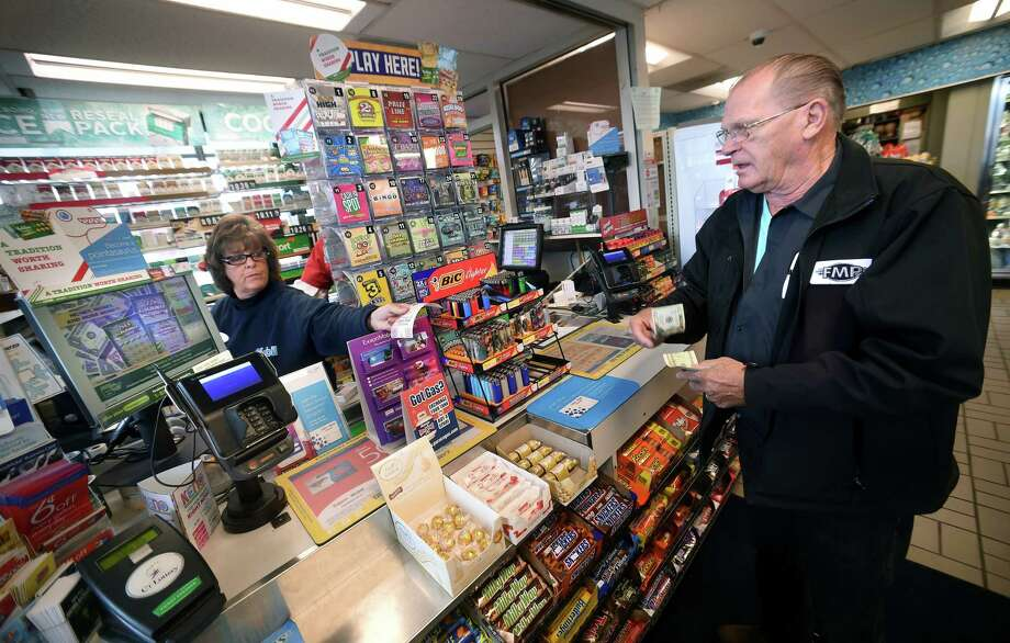 Joanne Dacunto (left) hands Eddie Jendrzewski of Branford his Mega Millions lottery tickets at the Mobil Mart on Leetes Island Road in Branford on October 23, 2018. Photo: Arnold Gold, Hearst Connecticut Media / New Haven Register