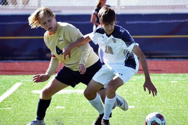 Father McGivney's Zach Hunter, right, battles with Althoff's Mitchell Kidd for possession during the first half of Saturday's sectional championship game in Belleville.