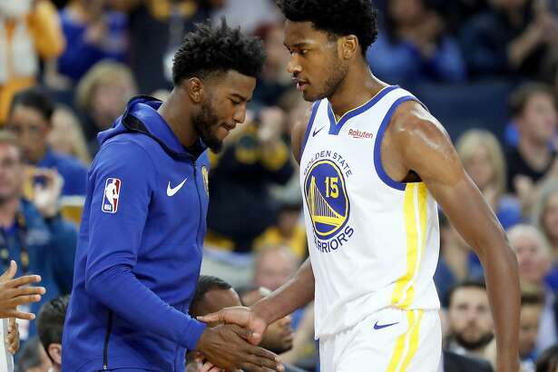 Golden State Warriors' Jordan Bell greets Damian Jones after Jones was removed in 1st quarter of 123-103 win over Phoenix Suns during NBA game at Oracle Arena in Oakland, Calif.. on Monday, October 22, 2018.