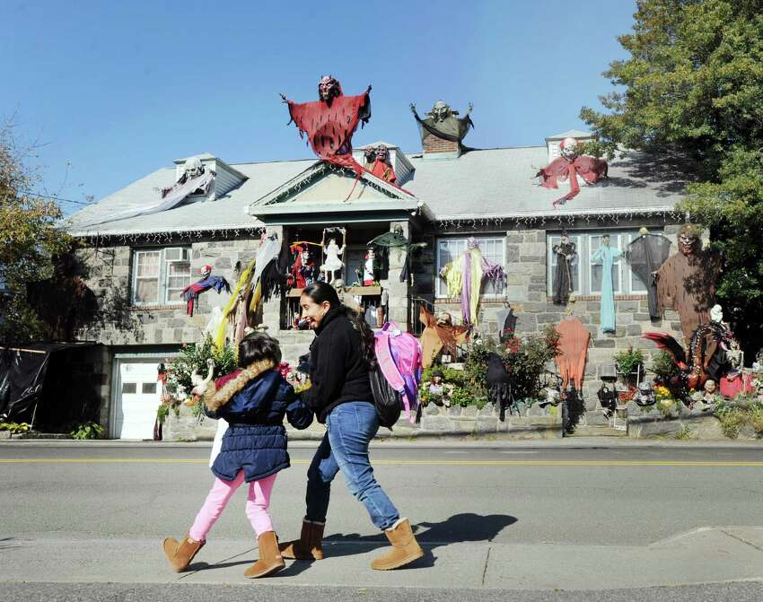 A woman holding a child's hand screams as she walks past Rosa Bruno's Halloween-decorated home on St. Roch Avenue in the Byram section of Greenwich, Conn., Tuesday, Oct. 23, 2018.
