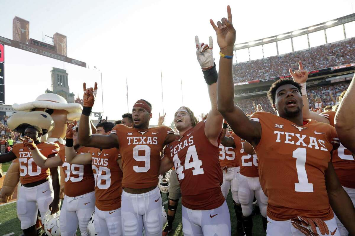 Texas wide receiver Collin Johnson (9) and defensive lineman Breckyn Hager (44) celebrate their win over Baylor with teammates Oct. 13 in Austin.