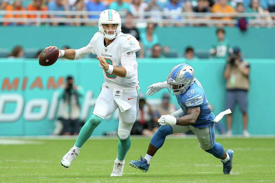 MIAMI, FL - OCTOBER 21: Brock Osweiler #8 of the Miami Dolphins scrambles away from Quandre Diggs #28 of the Detroit Lions during the second half at Hard Rock Stadium on October 21, 2018 in Miami, Florida.
