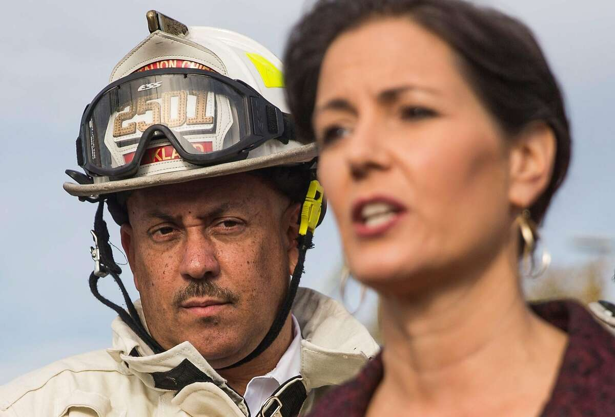 Oakland Fire Chief Darin White listens as Oakland Mayor Libby Schaaf speaks during a press conference as crews battle a massive blaze that destroyed six apartment buildings in different phases of construction near West Grand Avenue and Filbert Street in Oakland, Calif. Tuesday, Oct. 23, 2018.