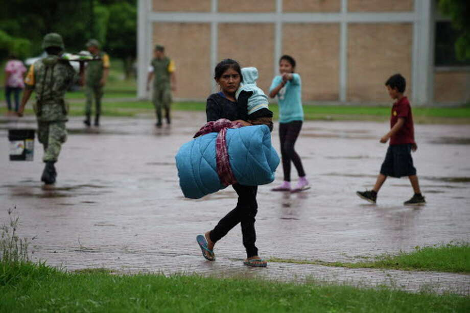 A woman carries her baby at an improvised shelter in Escuinapa, Sinaloa state, Mexico, on October 23, 2018, before the arrival of Hurricane Willa.  Photo: ALFREDO ESTRELLA, AFP/Getty Images / AFP or licensors