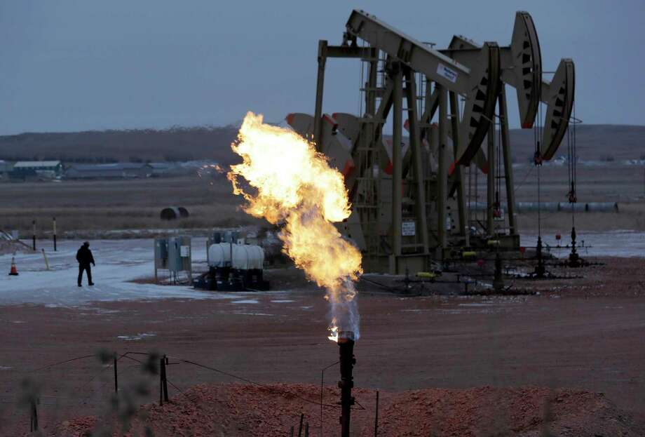 Workers tend to oil pump jacks behind a natural gas flare near Watford City, N.D in this 2015 photo. The Republican-controlled Congress is moving to overturn an Obama administration rule intended to clamp down on oil companies that burn off natural gas during drilling operations on public lands. Photo: Eric Gay, STF / Associated Press / Copyright 2016 The Associated Press. All rights reserved. This material may not be published, broadcast, rewritten or redistribu