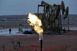 Workers tend to oil pump jacks behind a natural gas flare near Watford City, N.D in this 2015 photo. The Republican-controlled Congress is moving to overturn an Obama administration rule intended to clamp down on oil companies that burn off natural gas during drilling operations on public lands.