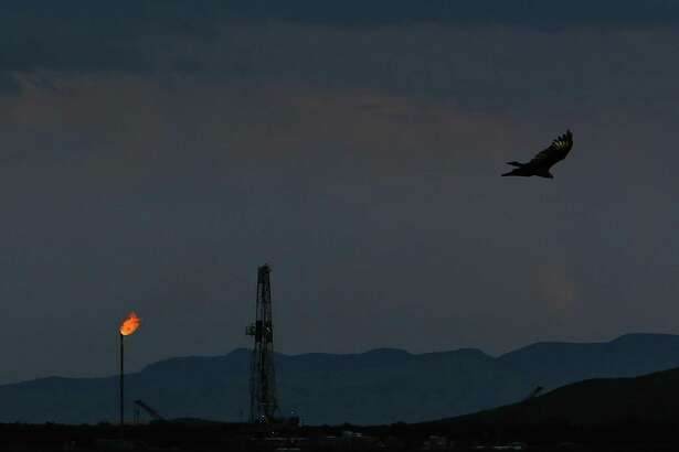A vulture soars over an Apache Corporation flare and drilling rig north of the Davis Mountains Friday, Sept. 16, 2016 in Balmorhea. The company recently announced the discovery of an estimated 15 billion barrels of oil and gas in the area and plans to drill and use hydraulic fracturing on the 350,000 acres surrounding the town. Apache has leased the mineral rights under the town and nearby state park, but has promised not to drill on or under either. While some residents worry that the drilling could affect the spring at the state park and impact tourism, others are excited for the potential economic boom the oil discovery and drilling could bring. ( Michael Ciaglo / Houston Chronicle )