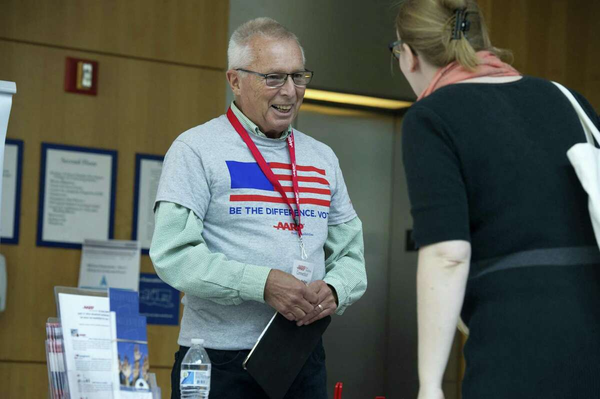 AARP volunteer Peter Eder, of Darien, talks about registering to vote while promoting a retirement security program without endorsing any candidate during the Voter Education Day event at UConn Stamford in downtown Stamford, Conn. on Tuesday, Oct. 23, 2018. The event was hosted by UConn Stamford professor Beth Ginsberg and her Electoral Behavior class and provided a variety of political perspectives and groups.