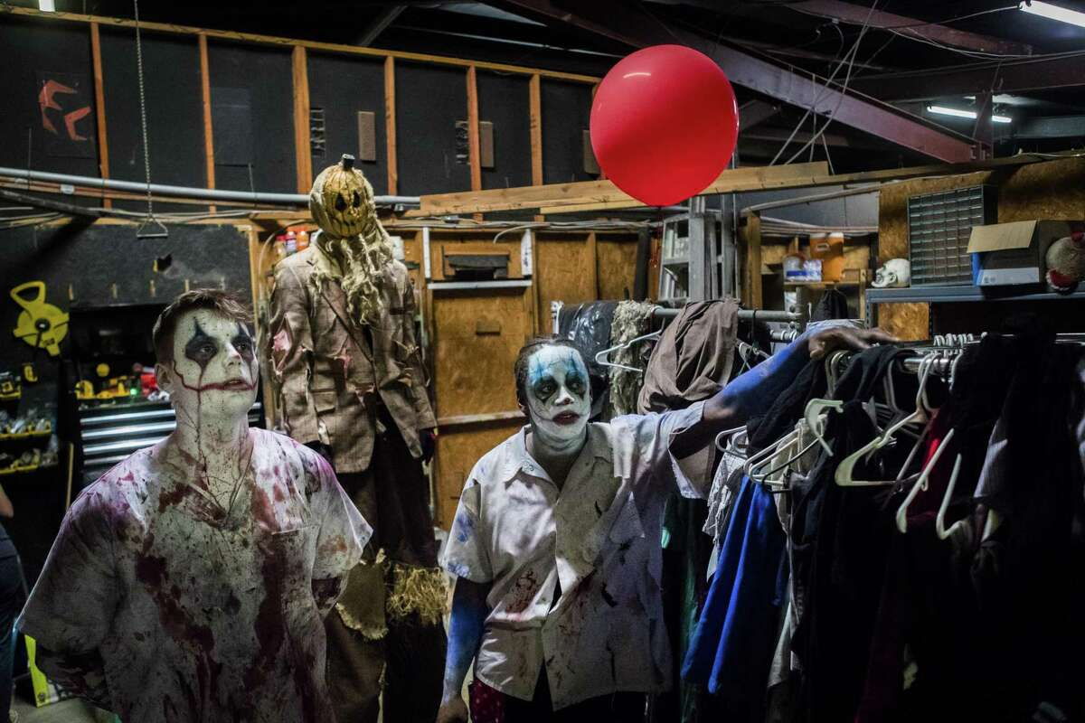 ScreamWorld performers gather for a staff meeting before the opening of the hunted house, Friday, Oct. 12, 2018, in Houston.