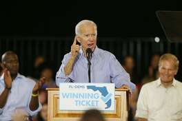 Former Vice President Joe Biden gives a speech to a packed gymnasium while Florida Gubernatorial Democratic candidate Andrew Gillum, left, and U.S. Sen. Bill Nelson looks on during the Florida Democratic Party rally held at the University of South Florida in Tampa, Fla., on Monday, Oct. 22, 2018. (Octavio Jones/Tampa Bay Times/TNS)