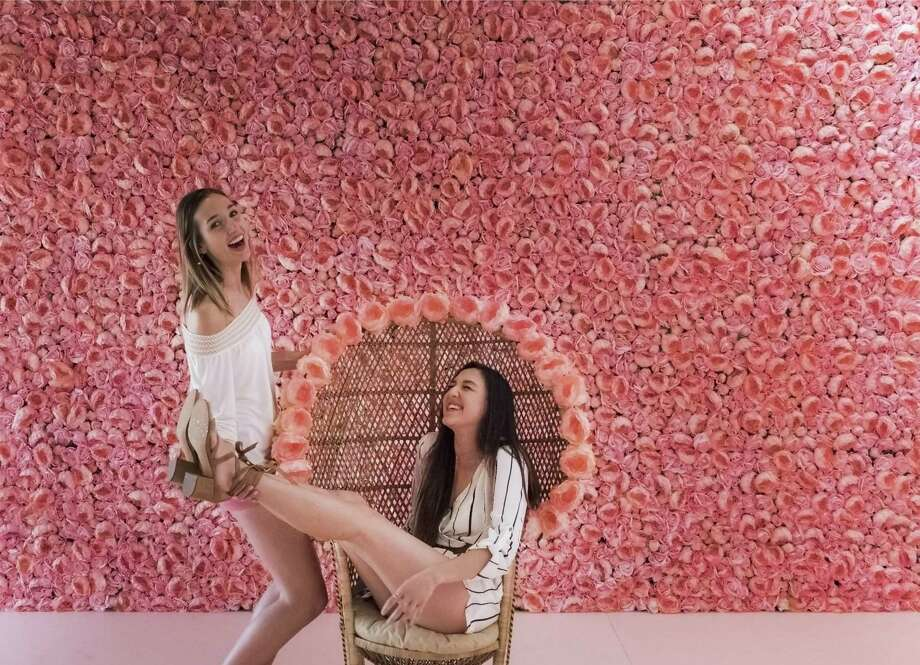 Ari Cowan (right) and Kristi Ellis have fun trying to figure out how to pose in front of a wall of pink flowers at Flower Vault. Photo: Kin Man Hui,  Staff / San Antonio Express-News / ©2018 San Antonio Express-News