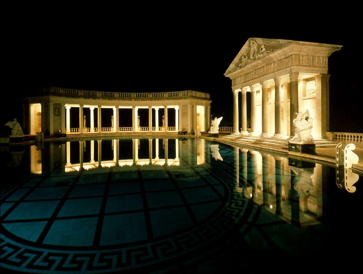 The Neptune pool is lit at night, accentuating the Greek columns and temple facade, at Hearst Castle in San Simeon, California.