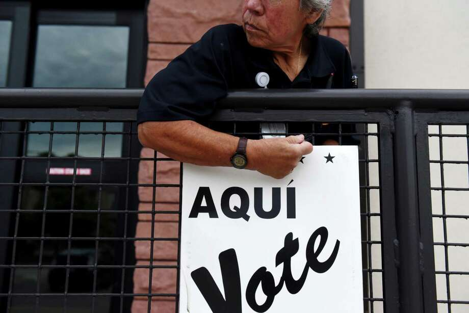A Bexar County employee sets up signs during early voting at a polling location in San Antonio, Texas, U.S., on Monday. Resist the temptation to vote straight party ticket — all parties have flawed candidates. Photo: Callaghan O'Hare /Bloomberg / © 2018 Bloomberg Finance LP