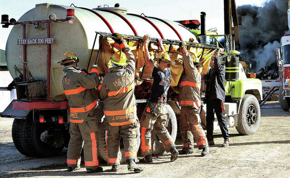 It took a small army of rural firefighters to extinguish the burning cars and other debris piled about 50 feet high. Firefighters work to unload one of the storage tanks they use to hold portable water in rural areas where no fire hydrants are nearby. The closest hydrant Tuesday was four miles away.
