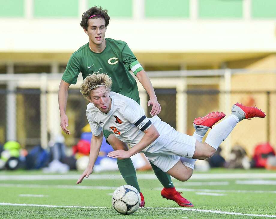Trinity Catholic Ben Lunny (3) advaces the ball past Stamford's Joshua Labkoff (8) as he falls to the turf in a battle at midfield for control during a varsity boys soccer match at Gaglio Field on Tuesday, Oct. 23, 2018 in Stamford, Connecticut. Stamford defeated Trinity 6-2. Photo: Matthew Brown / Hearst Connecticut Media / Stamford Advocate