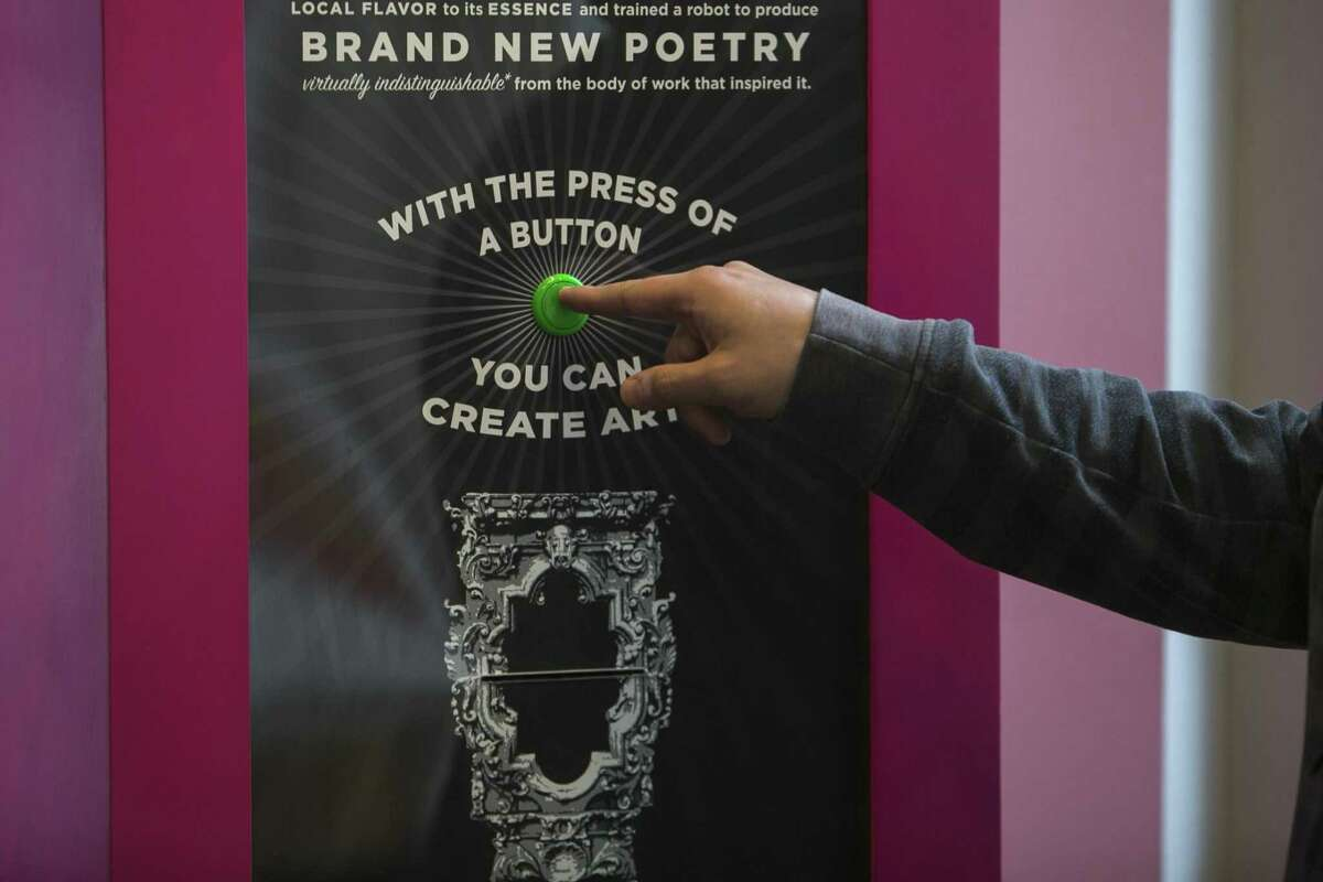 Stevan Zivadinovic pushes the button of the Word Salsa poetry kiosk to create and print a poem.