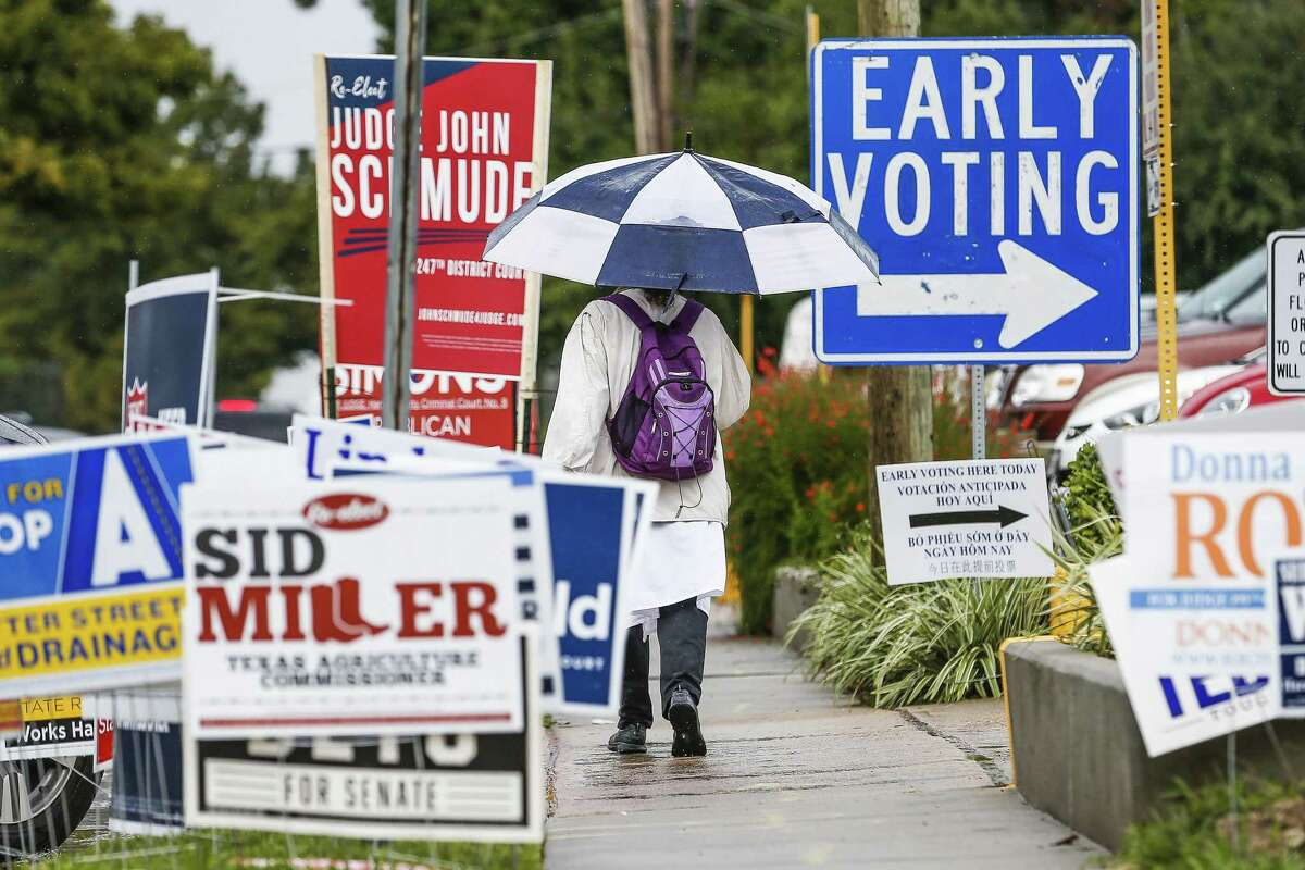 A woman walks past campaign signs as people brave the rain to head to the polls for the second day of early voting at the Trini Mendenhall Community Center Tuesday Oct. 23, 2018 in Houston.