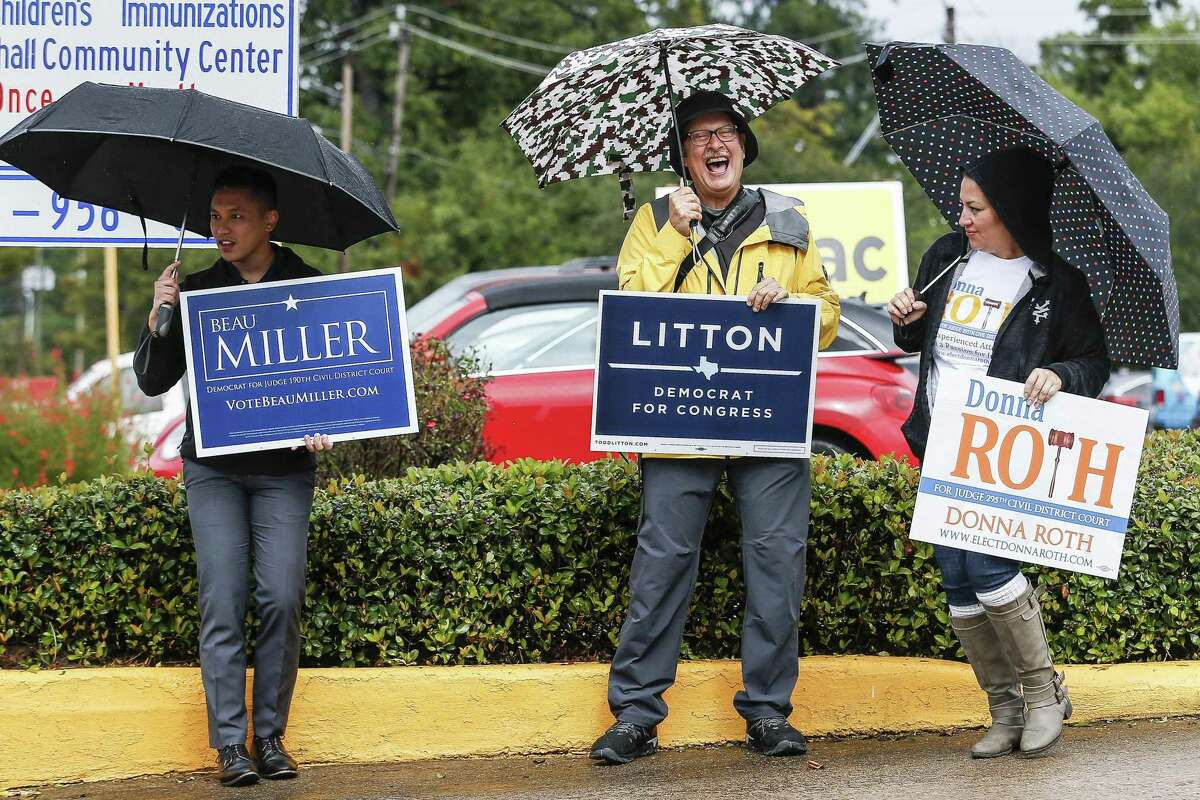 From left, Hosseh Enad, Lee Bryant and Sara Garcia stand under the cover of their umbrellas as they campaign outside the Trini Mendenhall Community Center for the second day of early voting Tuesday Oct. 23, 2018 in Houston.