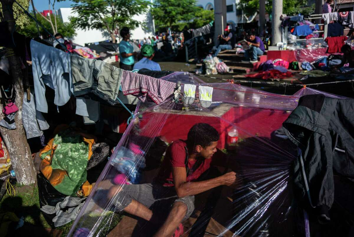 A Central American sits under a makeshift tent in Huixtla on Tuesday. The normal route north for migrants requires paying thousands of dollars to cartel-linked smugglers.