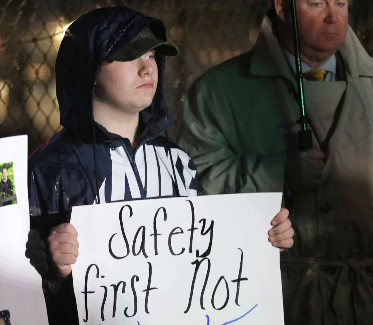 Saratoga Springs High School tenth grader Hunter Coons holds a sign supporting re-arming school monitors outside Saratoga Springs High School before attending the Saratoga Springs School District's Board of Education meeting Tuesday, October 23, 2018. Retired NYS trooper John Neeley stands at right. (Ed Burke photo-Special to The Times Union)