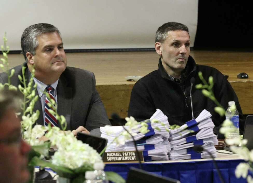 Delivered by district students, piles of petitions supporting re-arming school monitors sit in front of school Superintendent Michael Patton, left, and Board President Brad Thomas during the Saratoga Springs School District's Board of Education meeting at the high school Tuesday, October 23, 2018. (Ed Burke photo-Special to The Times Union)