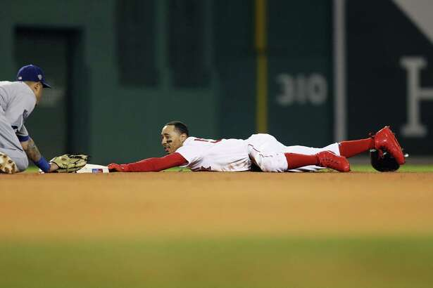 BOSTON, MA - OCTOBER 23: Mookie Betts #50 of the Boston Red Sox steals second base during the first inning against Manny Machado #8 of the Los Angeles Dodgersin Game One of the 2018 World Series at Fenway Park on October 23, 2018 in Boston, Massachusetts.