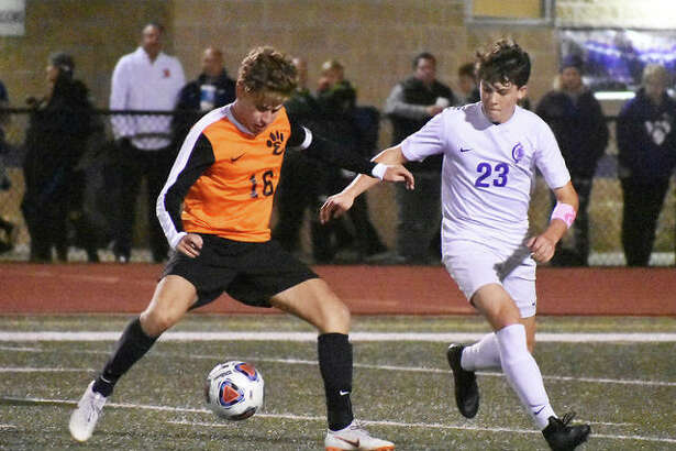Edwardsville midfielder Josh Reed battles Collinsville's Spencer Vlasak for possession of the ball during the first half.