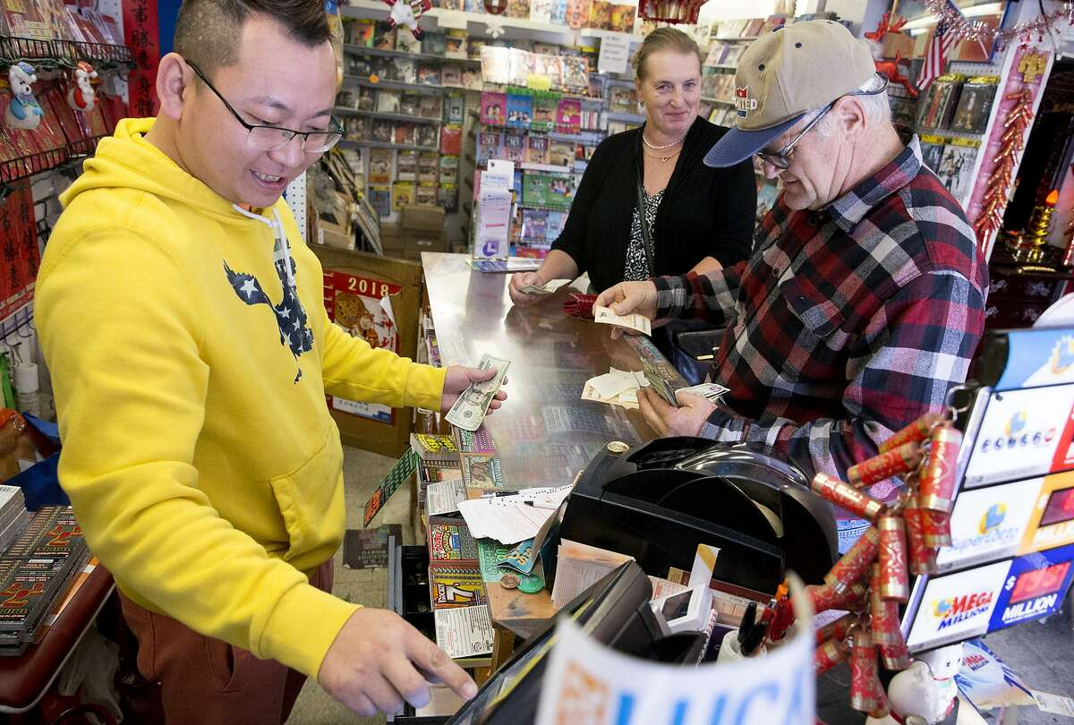 An employee of Lucky Day liquor store who wished not to be named sells Mega Millions lottery tickets to customers in Oakland, Calif. Tuesday, Oct. 23, 2018.